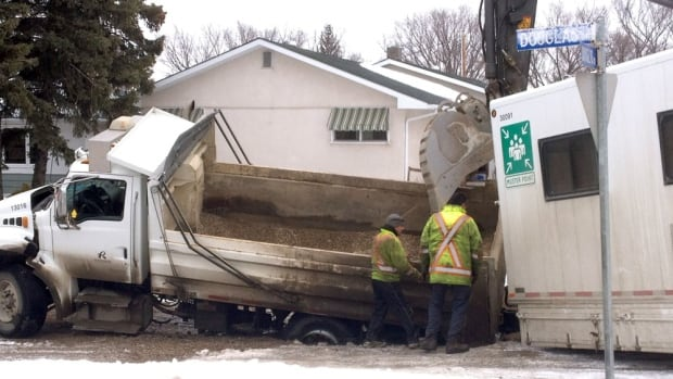 Efforts to fix a road in Regina's Dougas Park area hit a snag when the pavement gave way and a city truck fell into a sinkhole.