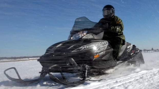 A Port aux Basques man was rescued by a friend after he was pinned under his snowmobile when a snow bank collapsed beneath him.