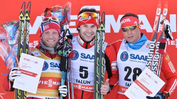 Canada's Alex Harvey, middle, poses on the winner's stand after the men's FIS World Cup cross country skiathlon race in Falun, Sweden on Saturday.