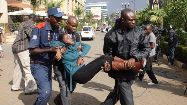In this Saturday, Sept. 21, 2013 file photo, a security officer helps a wounded woman outside the Westgate Mall after gunmen threw grenades and opened fire during an attack that left multiple dead and dozens wounded.