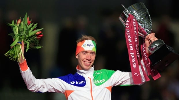 Jorrit Bergsma of the Netherlands celebrates holding the trophy on the podium after the men's 5000-metre speed skating race during the World Cup final at Thialf skating arena on Sunday in Heerenveen, Netherlands.