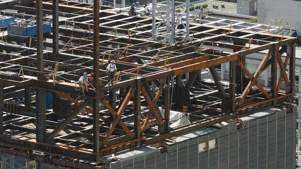 Workers fasten steel beams at a building construction site in Toronto.  Steel manufacturing was one of the factors driving up overall manufacturing sales in January.