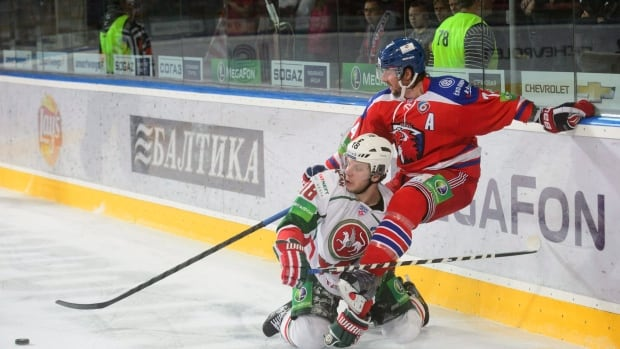 Mikhail Varnakov of AK BARS Kazan, left, and former NHLer Nathan Oystrick of HC Lev Praha, right, battle for the puck during a Kontinental Hockey League in September