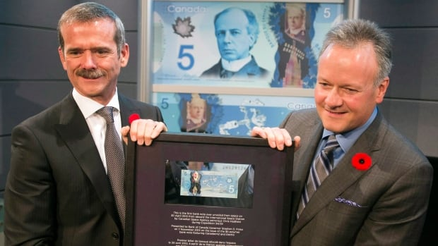 Canadian astronaut Chris Hadfield presents Bank of Canada Governor Stephen Poloz with the $5 bill he took into space. Maybe next time, it will be a coin.