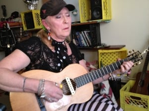 Nanci Blu playing her guitar