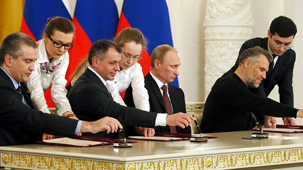 From left, Crimea's Prime Minister Sergei Aksyonov, parliamentary speaker Vladimir Konstantinov, a solemn Vladimir Putin and Sevastopol Mayor Alexei Chaliy attend an elaborate, state broadcast signing ceremony at the Kremlin on Tuesday, making the Ukrainian Black Sea peninsula a part of Russia.