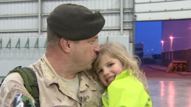 Warrant Officer Wilf Lowenberg kisses his daughter after he was reunited with his family Tuesday after spending nine months in Afghanistan.