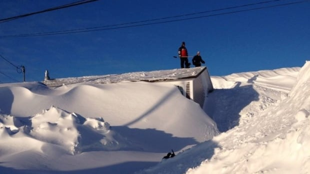 The home of Janice Gould and Rick Cooper in Port au Choix was buried in a mound of hard-packed snow, eight feet above the roof.