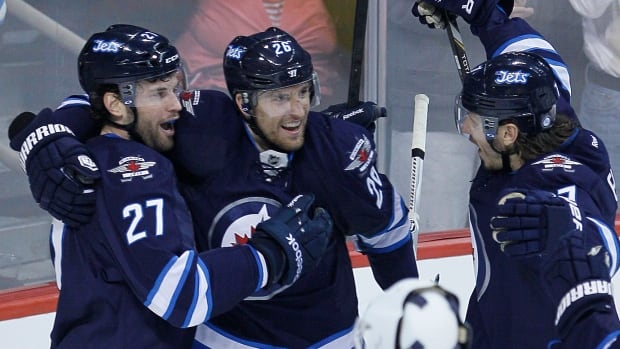 The Winnipeg Jets' Eric Tangradi (27), Blake Wheeler (26) and Keaton Ellerby (7) celebrate Tangradi's goal against Colorado Avalanche goalie Reto Berra during the first period Wednesday at the MTS Centre.