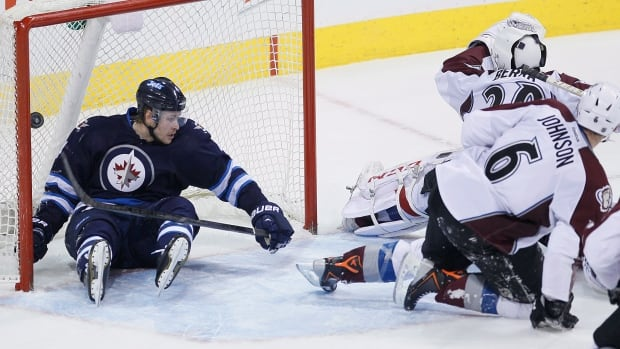 Winnipeg Jets' Paul Postma gets a front-row seat to Blake Wheeler's winning goal Wednesday night against Colorado Avalanche goaltender Reto Berra.