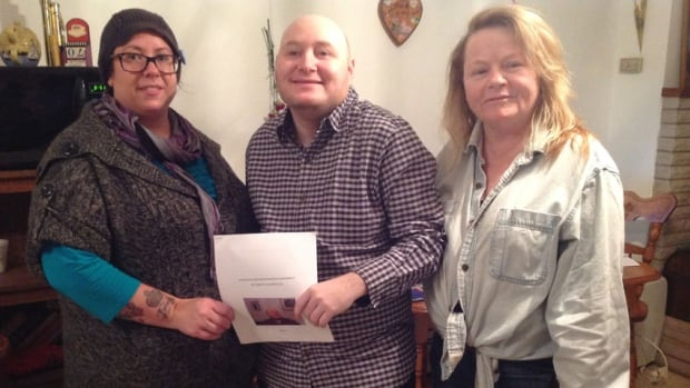 Jeremy MacDonald, with mother Terri (right) and friend Melissa Good, holds his supported decision-making document.