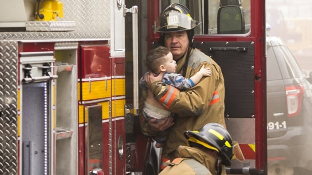 A firefighter rescues a 15-month-old boy from a house fire in north Hamilton on Thursday afternoon.
