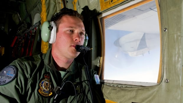 Royal Australian Air Force Loadmaster Sgt. Adam Roberts scans the ocean while onboard a C-130J Hercules as it flies over the southern Indian Ocean during Friday's search for missing Malaysian Airlines flight MH370.