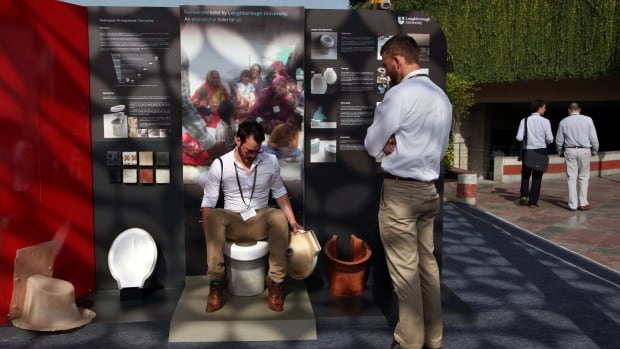 An exhibitor from Loughborough University demonstrates the use of a toilet during Reinvent The Toilet Fair in New Delhi, India.