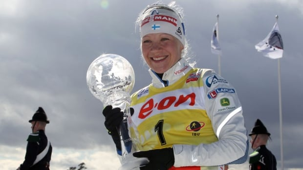 Kaisa Makarainen of Finland holds the trophy after clinching the biathlon World Cup title Sunday.