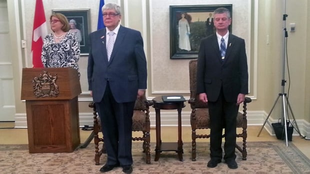Dave Hancock, Alberta's new interim premier, and George Vanderburg, Progressive Conservative party whip, stand during the swearing-in ceremony at Government House Sunday evening.