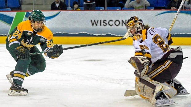 Clarkson's Shannon Macaulay, left, scores the game-winning goal against Minnesota goalkeeper Amanda Leveille in the third period of an NCAA college hockey game in the finals of the women's Frozen Four in Hamden, Conn., Sunday, March 23, 2014. Clarkson won 5-4.