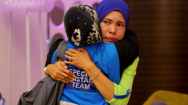 Families of the missing console one another in Kuala Lumpur. Lloyd's of London says it will begin paying out insurance claims on the flight.