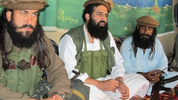 A Pakistani Taliban spokesman Shahidullah Shahid is pictured in Oct. 2013 flanked by his bodyguards. The Pakistani Taliban are about to meet for the first time with government officials, who are en route to a secret location described as a 'peace zone.'