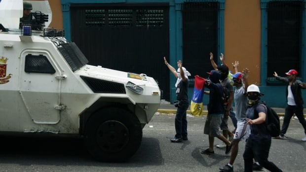 Anti-government protesters stand in front of a National Guard armoured vehicle during a protest in San Cristobal. A judge sentenced the city's mayor to one year in jail Wednesday after the government accused him of disobeying an order to take down protest barricades.