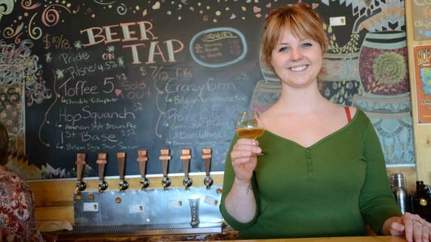 Prairie Sun Brewery co-owner Heather Williams shows off a glass of Meewasin 80 Ale. The beer is brewed with pine and spruce branches from along the Meewasin Valley.