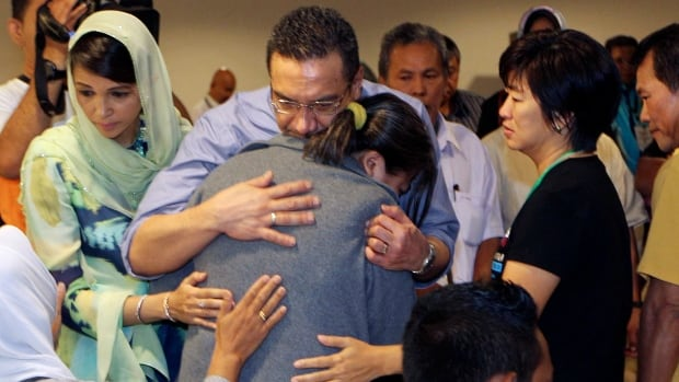 Malaysia's acting Transport Minister Hishammuddin Hussein, center, comforts a relative of passengers on board the missing Malaysia Airlines flight MH370 at a hotel in Putrajaya, Malaysia, Saturday March 29, 2014. Newly analyzed satellite data shifted the search zone on Friday, raising hopes searchers may be closer to getting physical evidence that Flight 370 crashed in the Indian Ocean on March 8 with 239 people aboard.