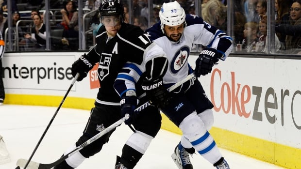 Los Angeles Kings center Anze Kopitar and Winnipeg Jets defenseman Dustin Byfuglien  battle for the puck during the third period of an NHL hockey game at the Staples Center on Saturday in Los Angeles.