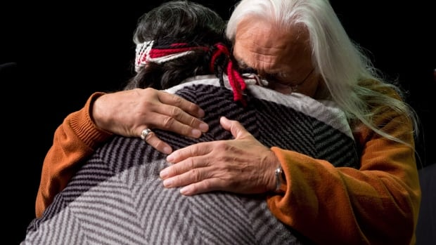 Residential school survivor Joe George, right, and elder Marie George embrace during a Truth and Reconciliation Commission event. A judge ruled Thursday that each survivor will decide if their testimony is preserved or destroyed.