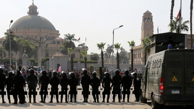 Riot police officers take positions in front of Cairo University plan a protest against former Defence Minister Field Marshal Abdel Fattah al-Sisi after he announced that he will run for presidential elections, March 30, 2014.