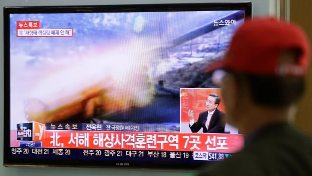 A man watches a television news program in South Korea reporting about North Korea's plan to conduct live-fire drills. South Korea and North Korea exchanged fire Monday, during which an unidentified drone fell on a South Korean border island.