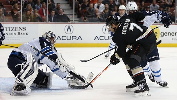 Ondrej Pavelec, left, and the Winnipeg Jets will try to fend off Andrew Cogliano, right, and the Ducks in Anaheim on Monday.