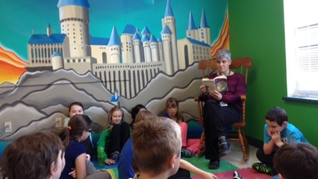 Ruth Clarke reads Harry Potter to her students by the Hogwarts mural.