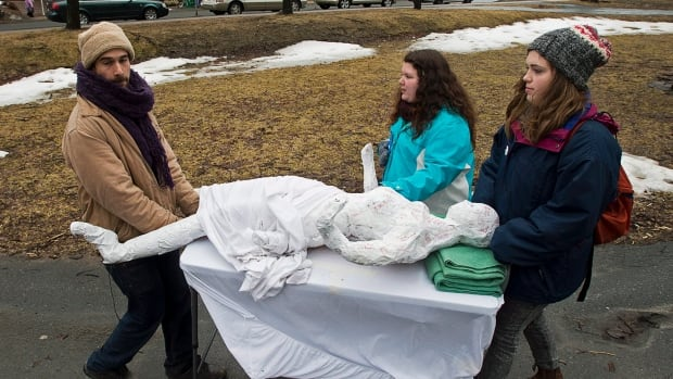 Protesters roll a mannequin on a gurney from Victoria Park, as they rally to support public health funding, in Halifax on Monday. Advocates fear Canadians may face bed shortages and more expensive drugs now that the 10-year, $41-billion health-care deal between Ottawa and the provinces has expired.