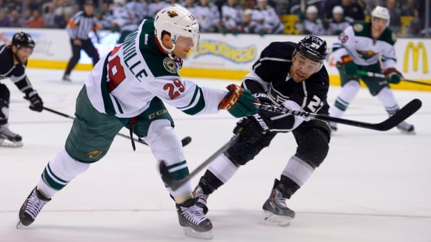 Los Angeles Kings defenseman Alec Martinez, right, attempts the block as Minnesota Wild right wing Jason Pominville takes a shot during the first period in Monday's game.