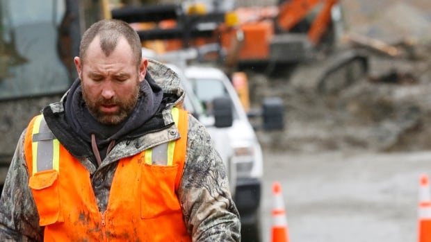 A rescue worker leaves a site after searching for victims of a mudslide in Oso, Wash., on Sunday. The death toll has reached 24 people, and 22 people are still believed to be missing.