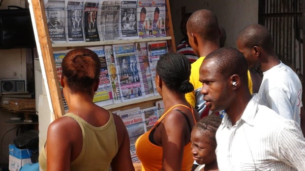 People read news headlines at a newsstand in Conakry, Guinea, on March 28.