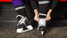 Child ties hockey skates in arena dressing room - 126932099