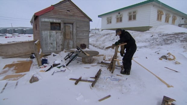 Joe Teemotee breaks down old shipping pallets to use for fuel in his woodstove. He's spent most of the past two decades living in a shack on the beach in Iqaluit, Nunavut.