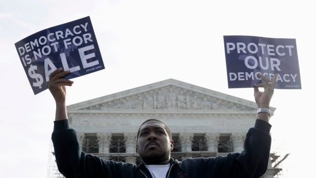 Cornell Woolridge of Windsor Mill, Md., takes part in a demonstration Oct. 8, 2013, outside the Supreme Court in Washington as the court heard arguments on campaign finance. Today the Supreme Court struck down limits on overall campaign contributions by big individual donors.