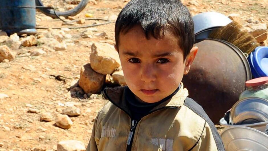 A Syrian refugee child who fled the violence from the Syrian town of Flita, near Yabroud, poses for a photograph at the border town of Arsal, in the eastern Bekaa Valley March 20, 2014.