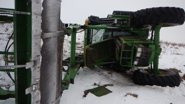 RCMP used a snowmobile to chase this stolen tractor through farmer's fields near Red Deer, Alta., before it rolled on a hill. The suspect driving the tractor was not injured.