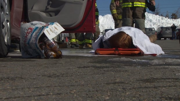 "A ""body"" lies next to a smashed case of beer as part of a mock accident in the Goulds area of St. John's on Friday."