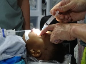 Art Rideout injects infant's lip with anesthetic