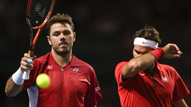 Switzerland's Stanislas Wawrinka, left, and compatriot Roger Federer react during their double match against Kazakhstan on Saturday in Geneva. FABRICE COFFRINI/AFP/Getty Images)