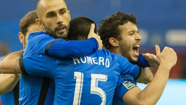 Impact's Marco Di Vaio, left, and Felipe Martins, right celebrate Andres Romero's first- half goal during MLS action against New York Red Bulls in Montreal on Saturday. Martins fired the equalizer in the 60th minute for a 2-2 tie.