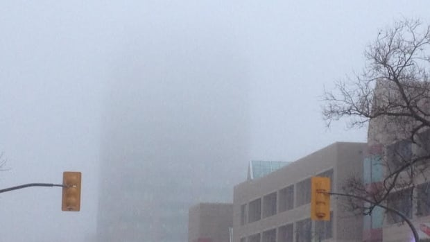 The top of the Investors Group building disappears into the Monday fog.