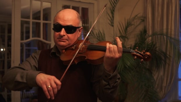 Soloist Ilya Kaler tests a violin during the study. Kaler wears modified welder goggles to prevent instrument identification by eye.