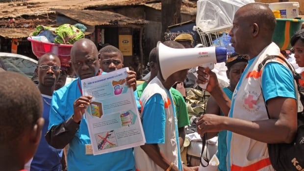 Health workers teach people about the Ebola virus and how to prevent infection,  in Conakry, Guinea, last month. Officials say more than 100 people have died in an outbreak of Ebola in West Africa.
