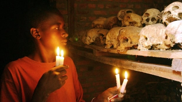 Apollan Odetta, a survivor of the 1994 Rwandan genocide, lights candles at a mass grave in Nyamata, Rwanda. It's estimated that between 800,000 and 1 million people, mostly Tutsis, were killed in the 100-day massacre.