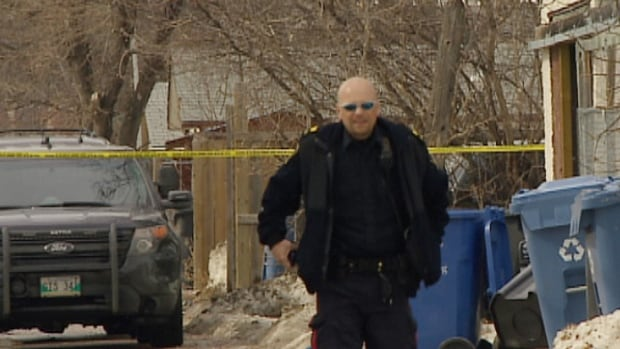 A police officer walks down an alley near the scene of a shooting on Monday in Winnipeg's North End.